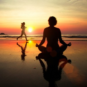 Concept of healthy lifestyle: Silhouette of a woman meditating on the beach at sunset, woman jogger in the background.
